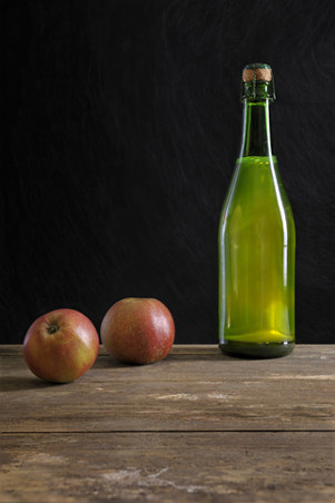 image cider bottle on table with apples