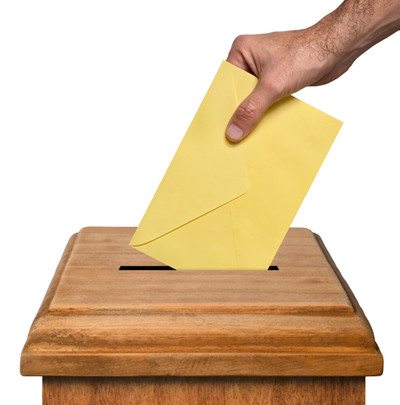 Voting, hand putting an envelope in a wooden box