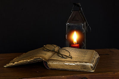 old book, a pair of glasses and a lantern
